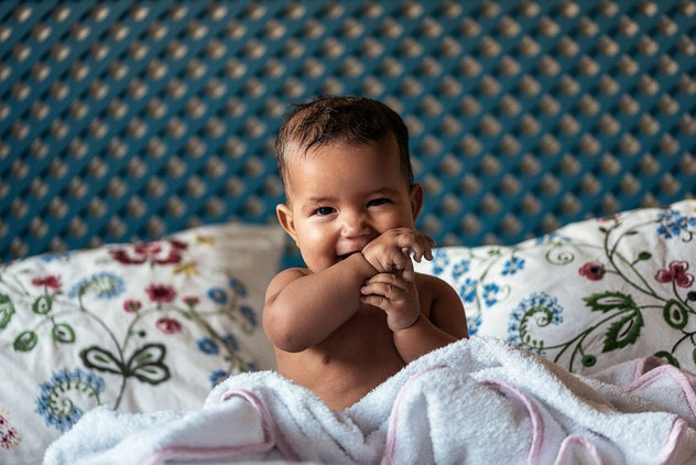happy baby sitting up in bed