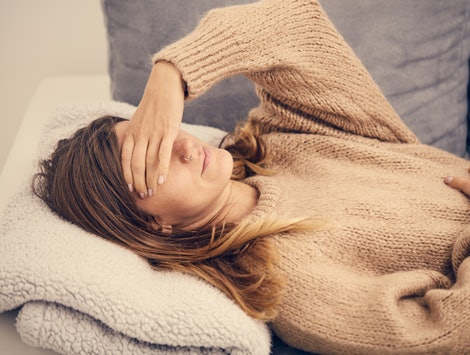 A woman lies on a couch wearing a sweater. Metabolism changes can affect your body in all kinds of ways.