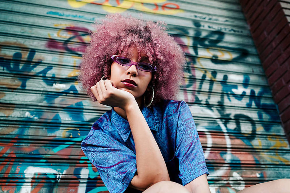 Young woman with pink hair in front of a graffitied background slaying the millennial game on social...