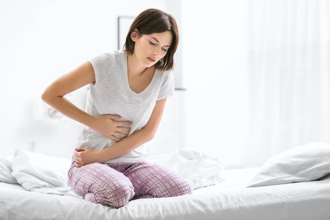 A person holds their abdomen while sitting on their bed. Your vagina can signal if your period is coming.