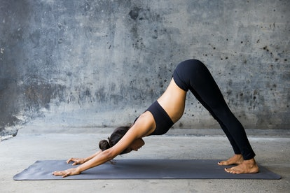 A woman in downward dog position. Some yoga poses can help relieve stomach bloat.