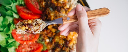 A woman eats a salad with quinoa and corn. Fiber rich foods can help your body's gut microbiome, which helps stomach bloat