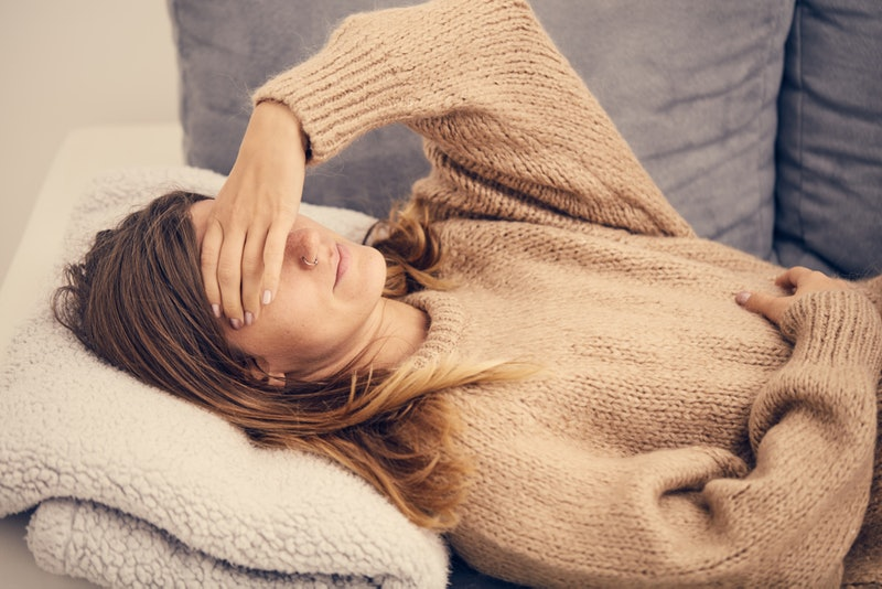 A woman wearing a sweater feeling cold and sweating at same time.