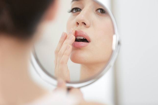 A person looks in the mirror, covering up a cold sore on their lip. Lips can tell you a lot about your health.