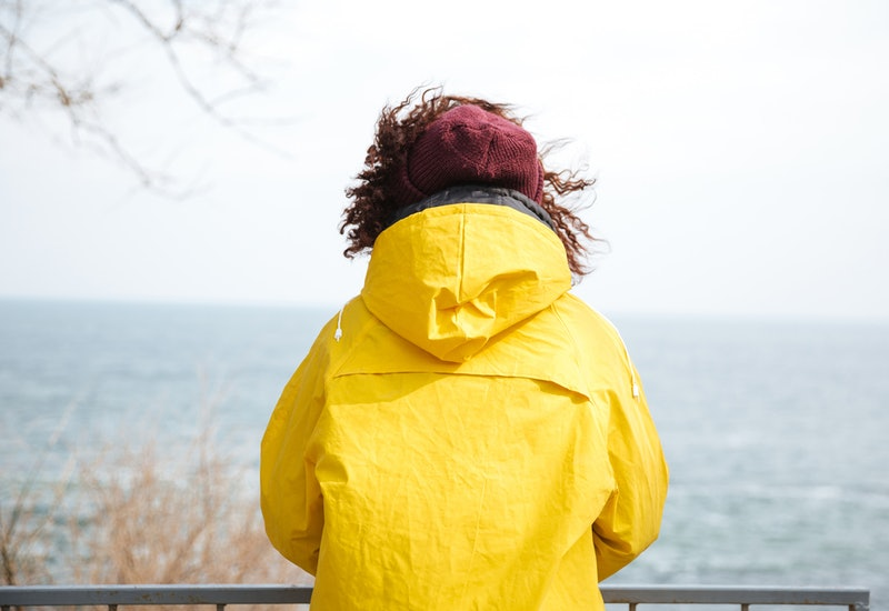 A woman in a yellow jacket looks out over a body of water. Here's how PTSD affects the brain, according to researchers