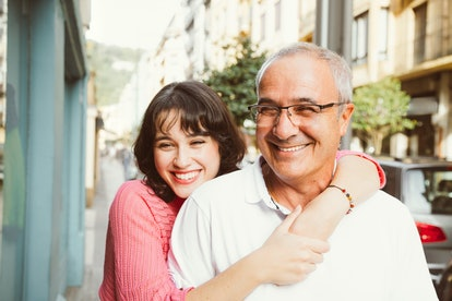 A woman smiles while wrapping her arms around her dad on a sunny day.