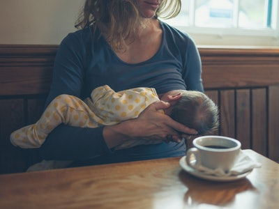 a breastfeeding mom with a cup of coffee