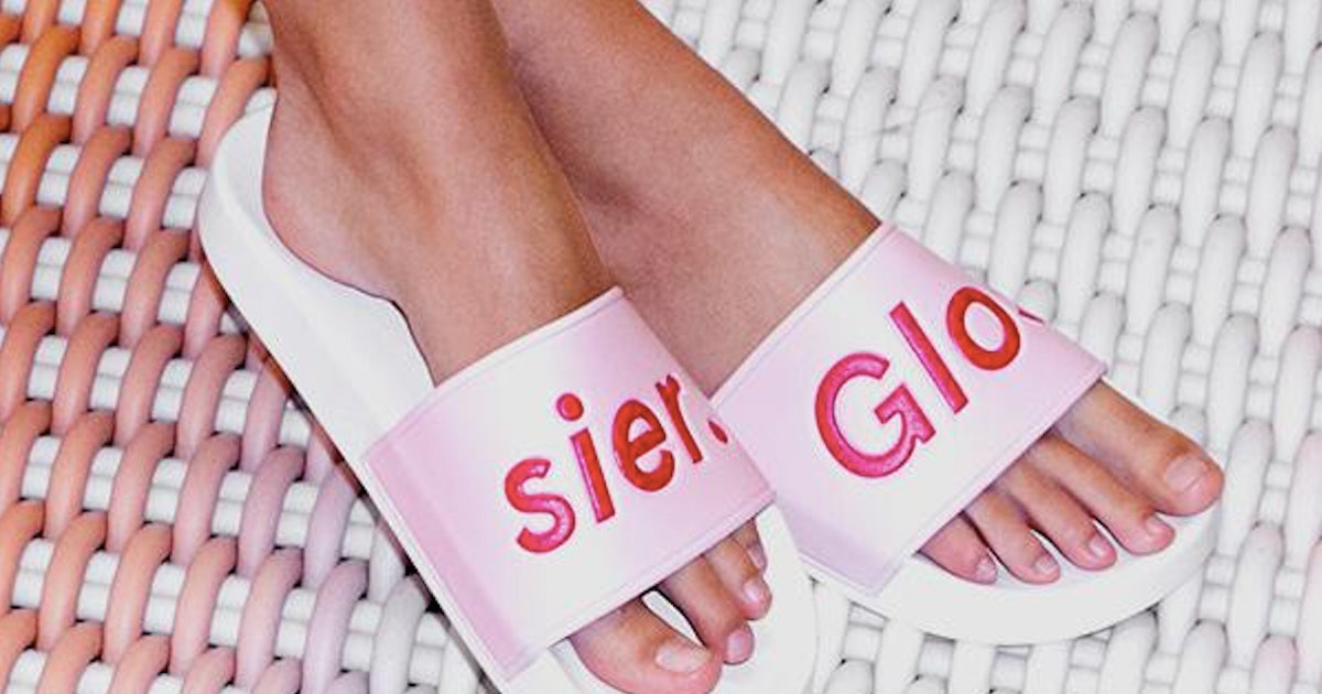What's In Glossier's Glossiwear Merch Collection? There Are Sliders, Sweaters & Hair Clips Galore