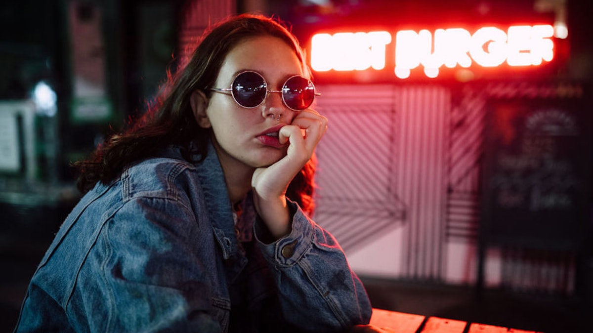 Young woman wearing sunglasses in front of neon sign that says Best Burger.