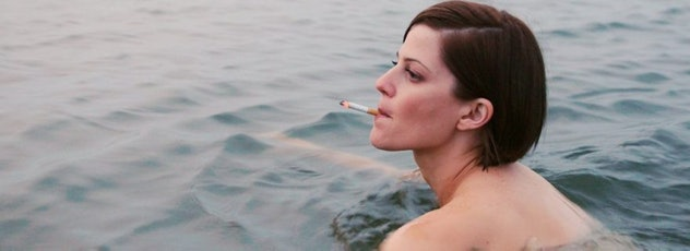 A still from the film Menorca, in which a beautiful woman smokes a cigarette whilst swimming.