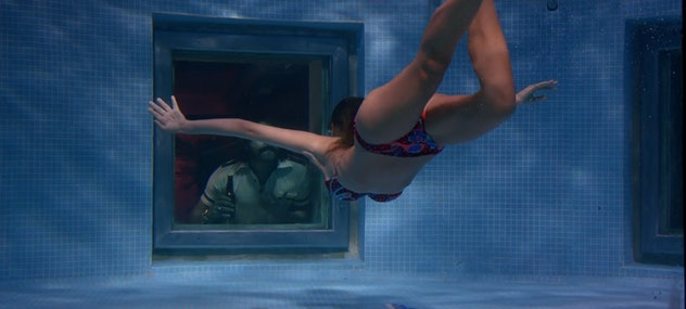 An underwater still from the film Desire, in which a woman in a bikini swims toward man in a window that is in the wall of a pool.