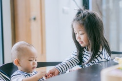 A little girl helping her baby brother, seated at a table