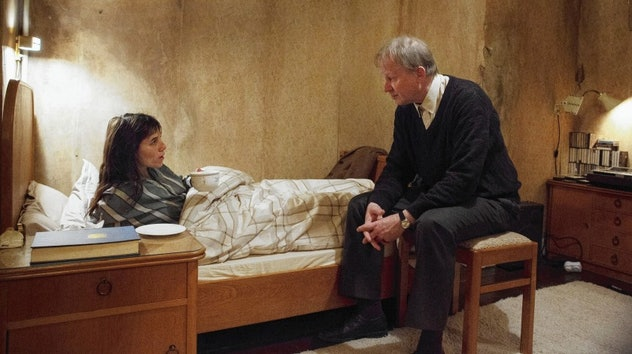In Nymphomaniac: Volume 1, Charlotte Gainsbourg's character lays in bed and talks to a man in a suit.