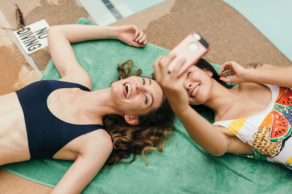Young woman taking a selfie with her sister to post on Instagram with sister birthday captions.