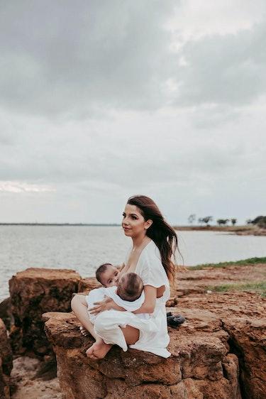 mom breastfeeding twins by the sea