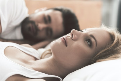 A woman and man lay in bed. The woman is looking up at the ceiling while the man sleeps.