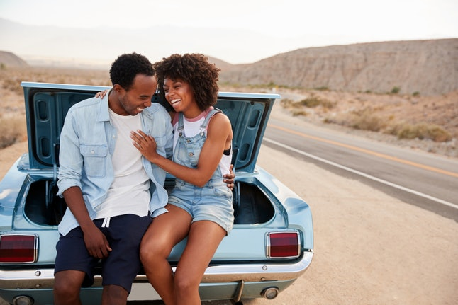 A couple sitting on the trunk of a car. Disconnecting from technology while traveling can make you feel free