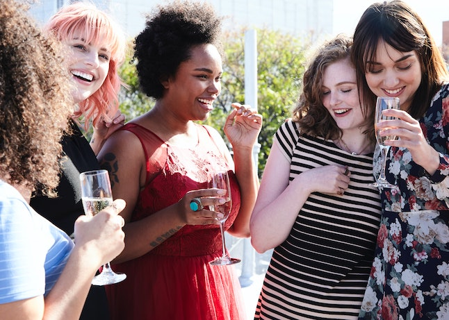 A group of women celebrating and drinking, similar to Galentine's Day on Parks & Recreation.