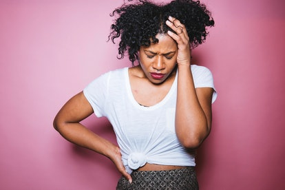 A woman with a PMS-related headache on a pink background. Period changes can be a sign your IUD has moved.