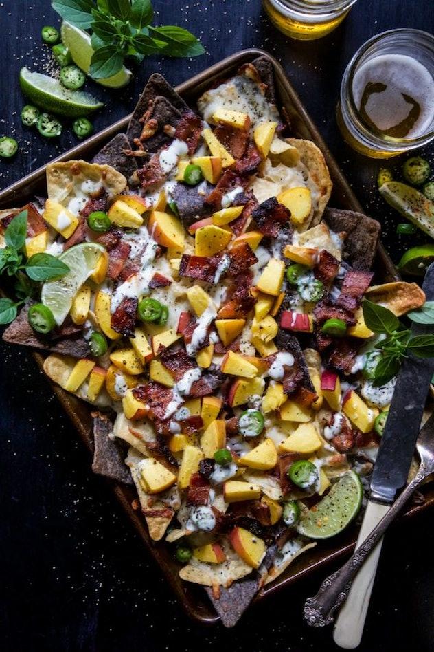 image of gluten-free sheet pan recipe- bacon peach nachos topped with jalapeno