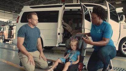 Adam Busby installing a car seat