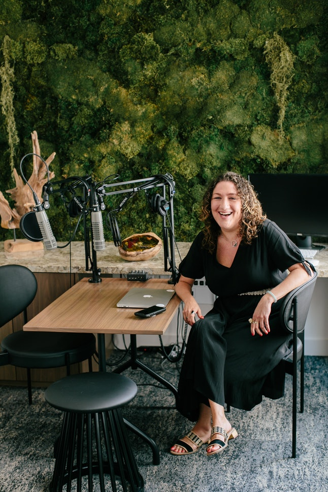 """Harper Spero sits at a table with podcast recording equipment. """"Made Visible"""" Podcast is for anyone who struggles with invisible illness"""