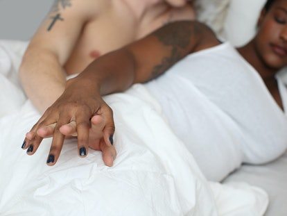 A couple cuddles in bed after having anal sex