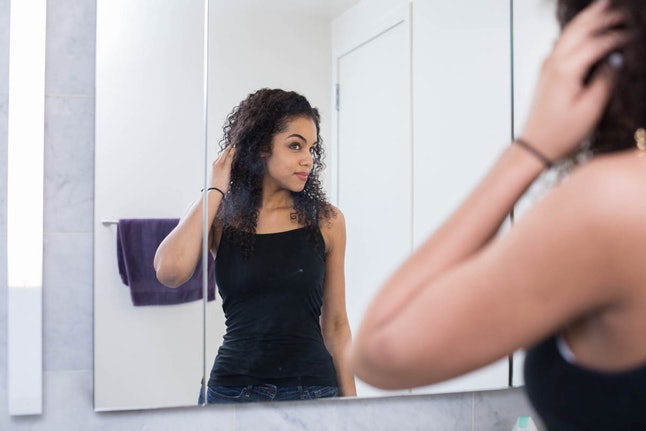 A woman looks at her own reflection in the mirror. It only takes three days to enjoy being alone and loving your own company.