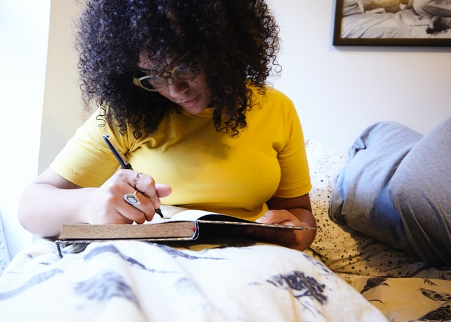A woman journals in bed. Being alone gives you time to work on new projects.