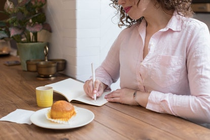 A woman journals at a wooden table with a muffin. In three days, being alone can give you perspective.