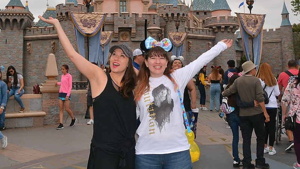 Two sisters wearing Mickey Mouse ears stand in front of Sleeping Beauty's Castle at Disneyland with their arms out.