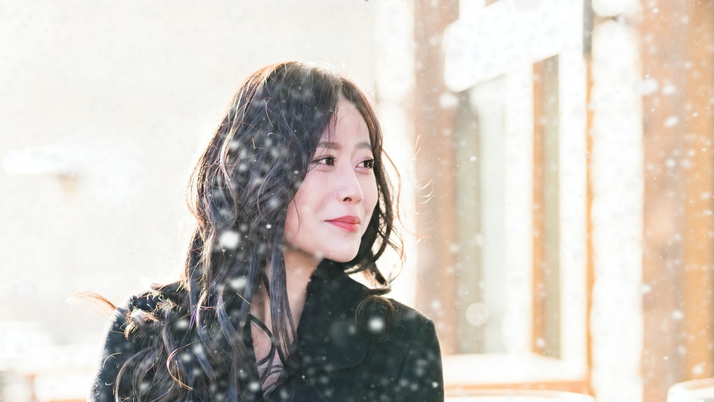 Young Asian woman walking in snow