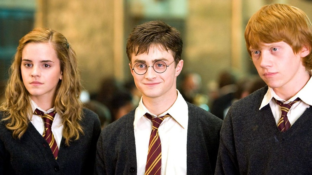Hermione, Harry, and Ron from 'Harry Potter' stand together in the Great Hall.