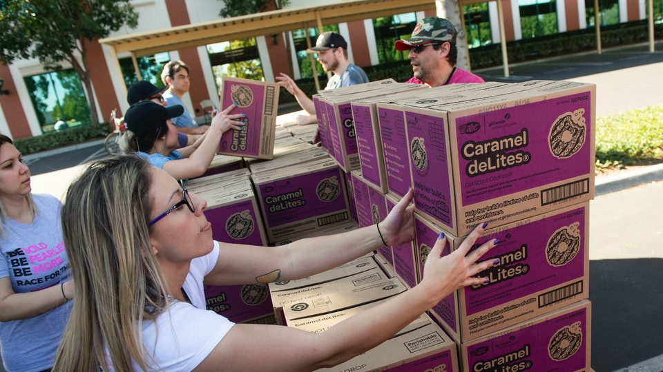 Volunteer Katie O'Neill, 29, of Orange, and several of her First American Title co-workers stack Caramel deLites as they load up vehicles during the Girl Scout Cookie Mega Drop at the Anaheim Business Complex in Anaheim