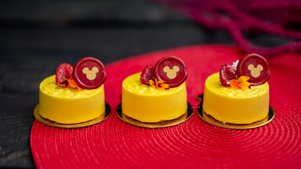 Three Disney Lunar New Year mango pineapple pastries with a Mickey Mouse decoration sit on a table.