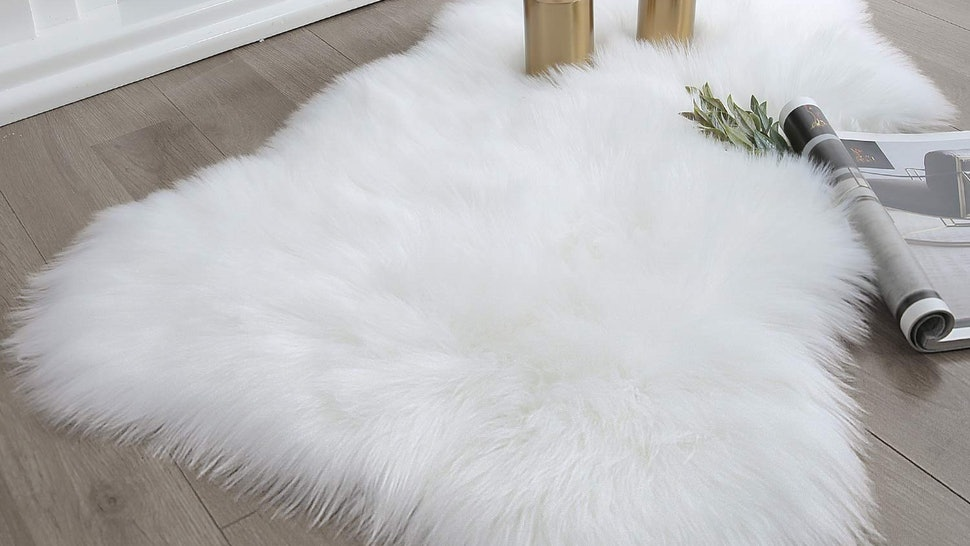 Gold candle holders sitting on a white faux fur rug, placed in front of a fire.