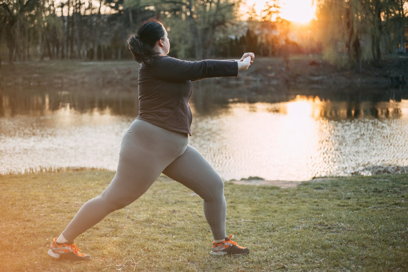 A person wearing a black shirt, grey leggins, and orange-laced sneakers leans into a yoga pose on some grass overlooking a body of water. Body-positive yoga videos can be difficult to come by, but they're well worth it when you find them.