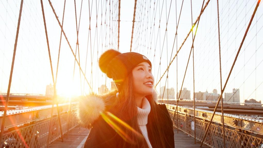 Young Asian woman crossing bridge in sunlight