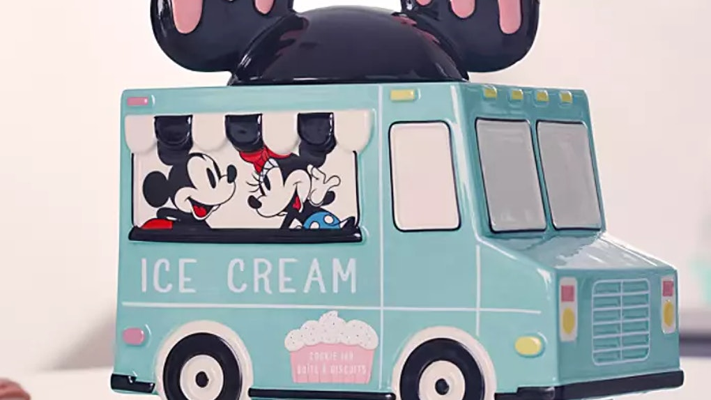 A Mickey and Minnie Mouse cookie jar shaped like an ice cream truck sits on a white kitchen counter.