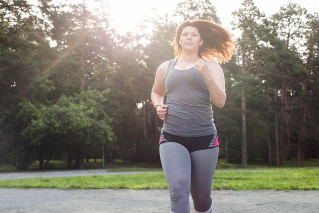 A person with her hair down and a tank top with shorts over leggings runs in a park. You can stretch before you run to help minimize risk of injury and get your body ready for your workout.