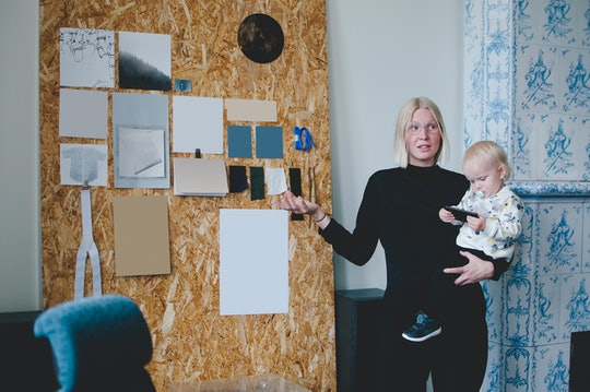 A baby holding a toddler points at a board during a meeting