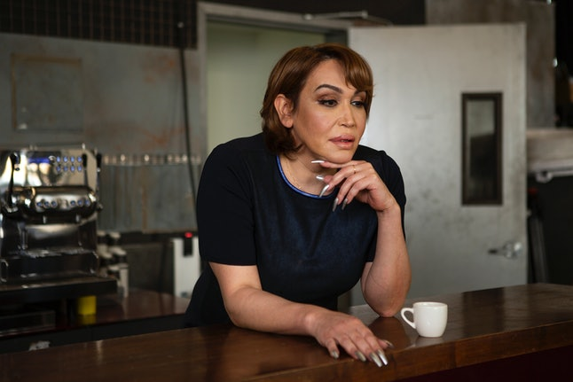 A transgender woman standing at a bar with her hand under her chin. Taking more breaks can actually help you be more productive at work.