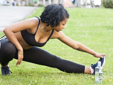A person wearing a black bra, running leggings, and a rainbow necklace stretches on a grassy field. Stretching before you run is important, but it's also important how you stretch.