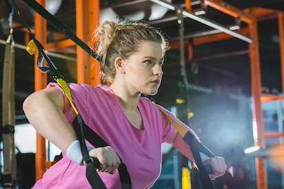 A person wearing a pink shirt and white wrist bands performs a TRX pushup. It's important to ask your potential personal trainer and therapist questions to make sure they're a good fit for you.