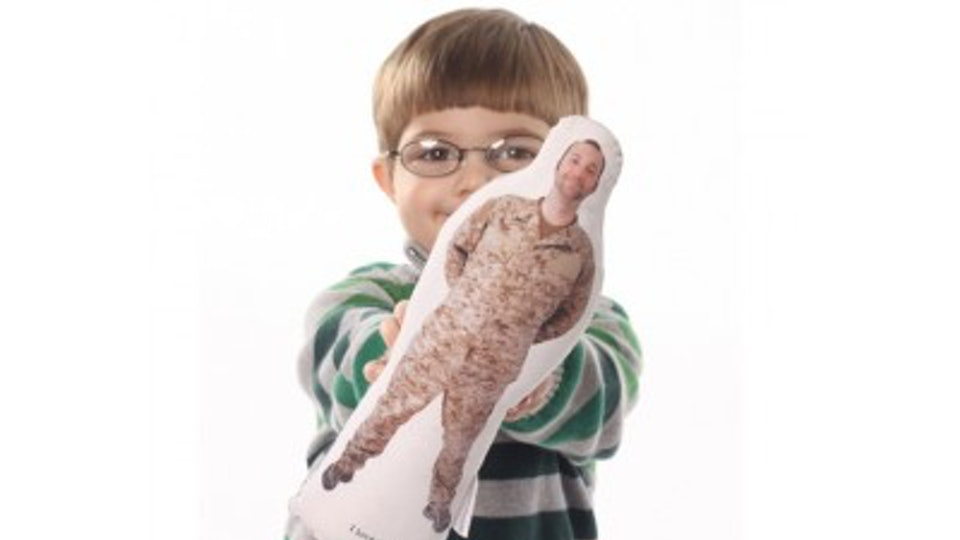a little boy holding a hug-a-hero doll
