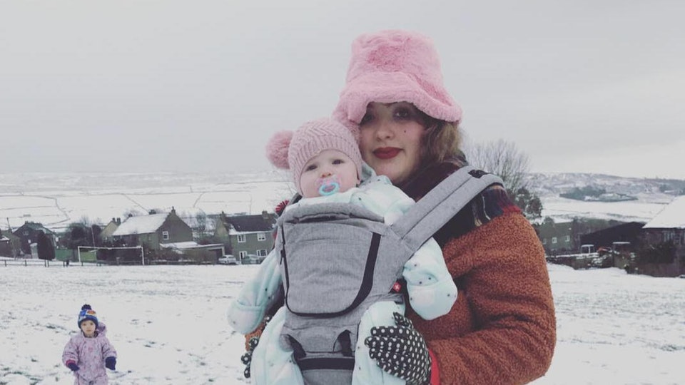 A mother stands in snowy field with a baby in front carrier and toddler in beanie on the ground.