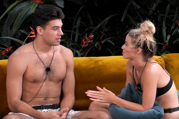 Elizabeth and Zac from 'Love Island' USA talk on a yellow couch at the villa in Fiji.