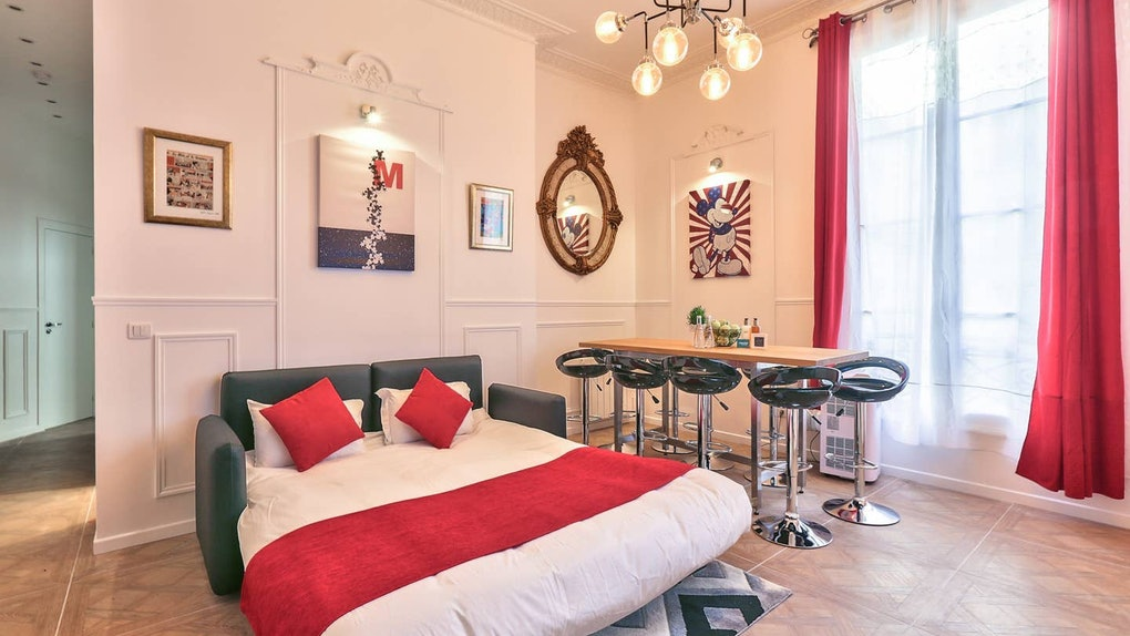 This Mickey Mouse-themed Airbnb in Paris has a leather pullout couch with red throw pillows, a big window, and Mickey decor throughout.