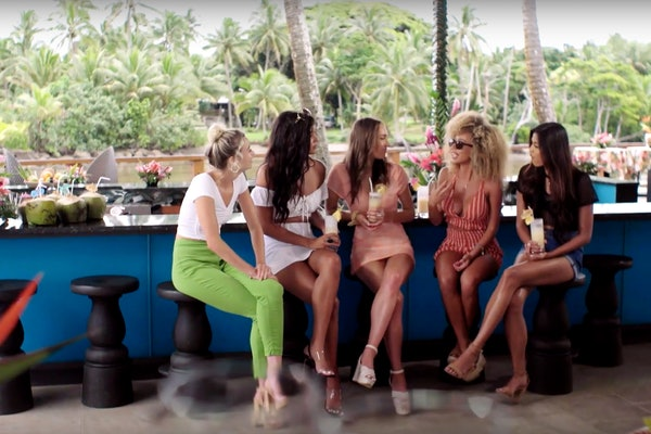 The Islanders of 'Love Island' sit and talk at a bar in the villa.