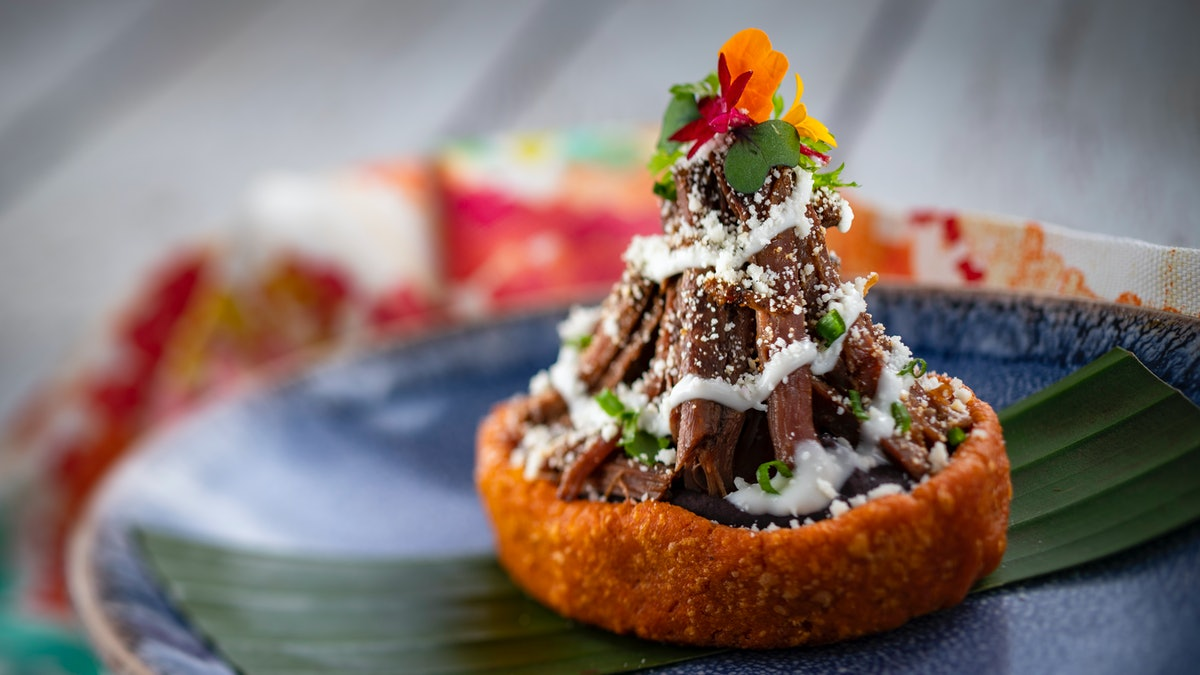 The barbecoa sopes served at Epcot's International Festival of the Arts sits on a plate.